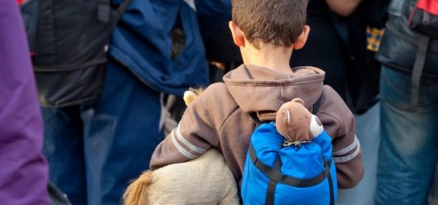 Flüchtlingskind mit Teddy im Rucksack